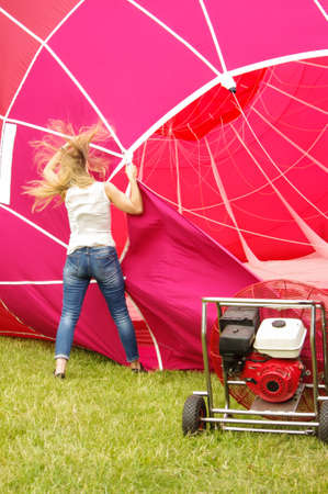 Girl holding hot air balloon material for inflating and prepare for flight