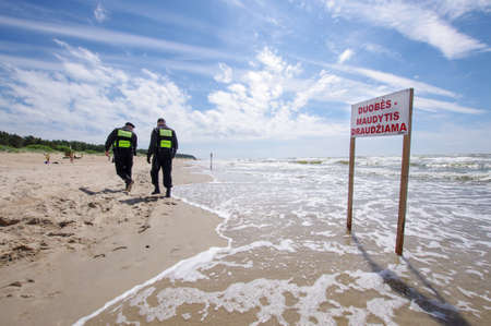 accidental: PALANGA, LITHUANIA - JUNE 20, 2017: Two policemans taking care on the beach and sign with bathing prohibition in lithuanian language in Palanga, Lithuania. Editorial