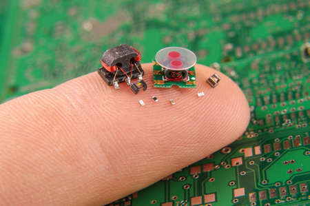 Small electronics components on human finger Imagens - 81307412