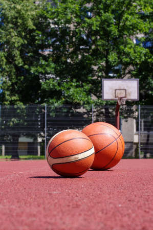 Two basketball balls on the ground of public court Stock Photo