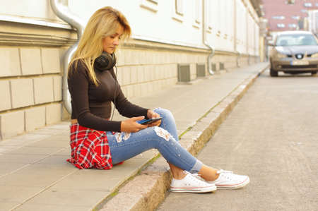 Young female sitting at the street and browsing smartphone