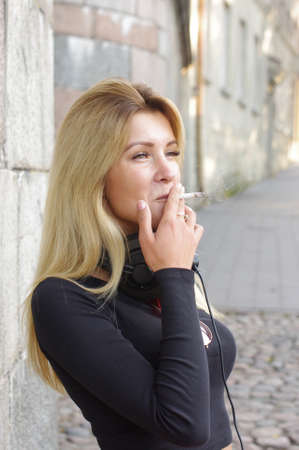 Young woman smoking in the city