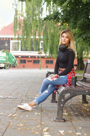 Urban style young female sitting in the city