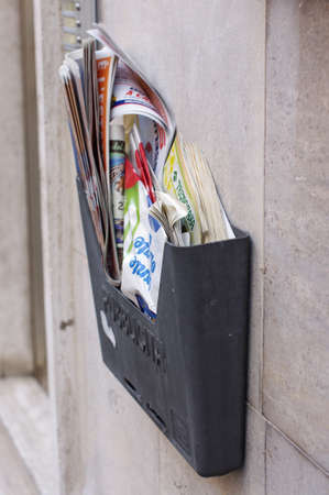 PISA, ITALY - JULY 30, 2017: Mailbox overfilled with spam on the wall of the house in Pisa, Italy. Stok Fotoğraf
