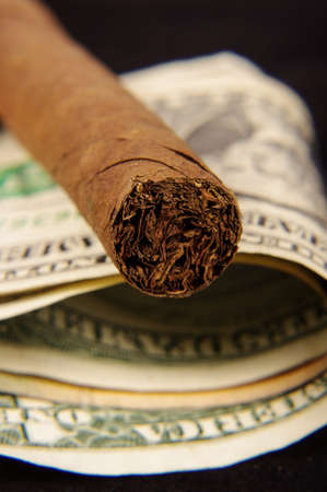 Expensive cigar on the dollar banknotes