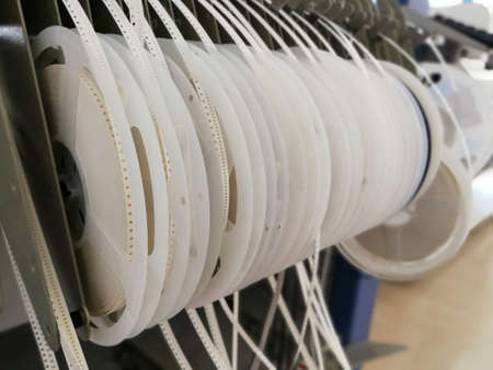 Paper reels with various electronic components resistors, capacitors, inductors close up Imagens - 99739433