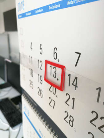 13th day marked with red calendar marker on the office wall calendar