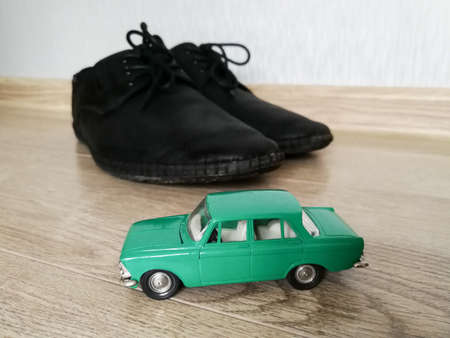 Car model toy in comparison with black male shoes Imagens
