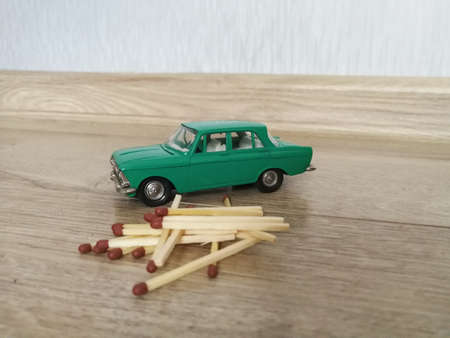 Car model toy in comparison with matches on the floor