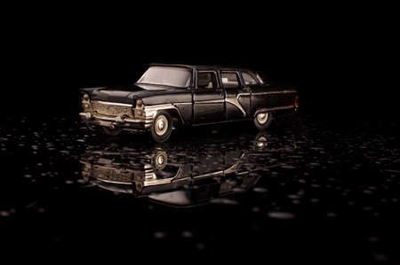Luxury black soviet car die cast model on the black reflective surface