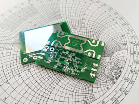 Radio frequency and microwave printed circuit board PCB in front of Smith chart Фото со стока
