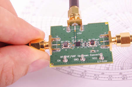 Radio frequency engineer inspect microwave mixer printed circuit board PCB in front of Smith chart