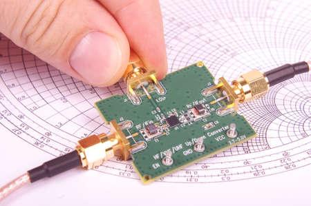 Ingegnere di radiofrequenza ispezionare il circuito stampato del mixer a microonde PCB davanti al grafico di Smith