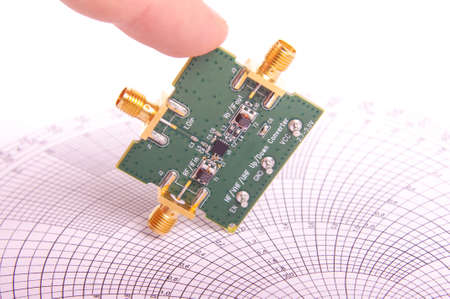 Radio frequency engineer inspect microwave mixer printed circuit board PCB in front of Smith chart Imagens