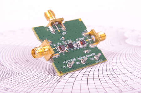 Radio frequency mixer printed circuit board PCB in front of Smith chart for microwave and RF calculations Banco de Imagens