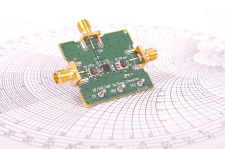 Radio frequency mixer printed circuit board PCB in front of Smith chart for microwave and RF calculations