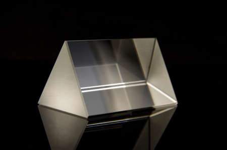 Triangular optical prism for scientific experiments isolated on the black reflective background