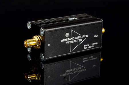 RF and microwave wideband signal amplifier isolated on the black reflective surface Фото со стока