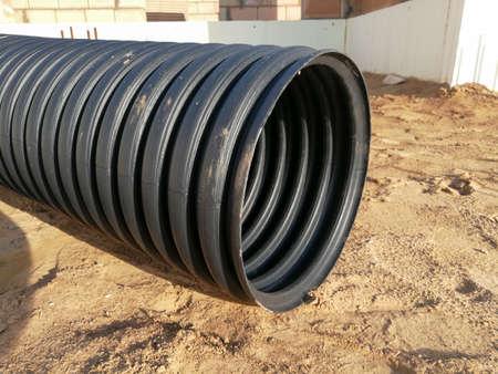 Perforated black PVC plastic drainage corrugated pipe for water canalization Archivio Fotografico