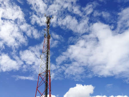 GSM (Global System for Mobile communication) base station and repeater tower in front of blue cloudy sky 版權商用圖片