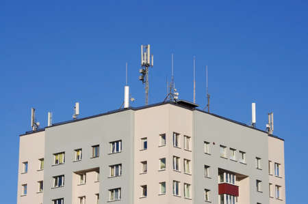 GSM and television antennas on the roof of the building in front of blue sky
