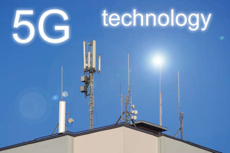 5G, GSM and television antennas on the roof of the building in front of blue sky Banque d'images