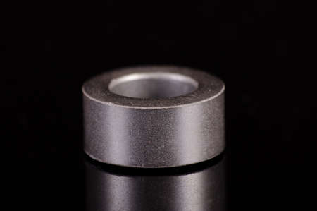 Ferrite core ring in the shape of toroid isolated on the black reflective background Stock fotó