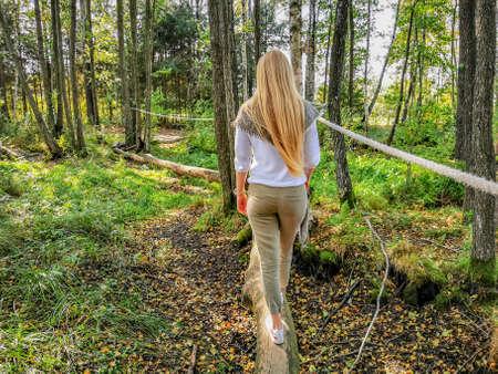 A girl walking a log through a swamp in autumn