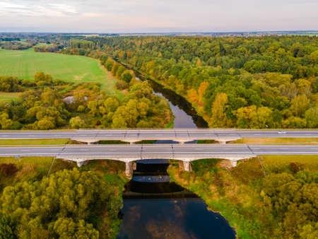 Aerial view of forest full of autumn colors with highway and river crossing it Stock fotó