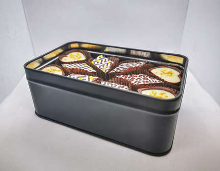 Selection of delicious hand made luxury chocolate candies in a black metal gift box