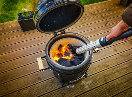 Lighting a Kamado type barbecue grill with an electrical charcoal lighter. Black kamado cook stove