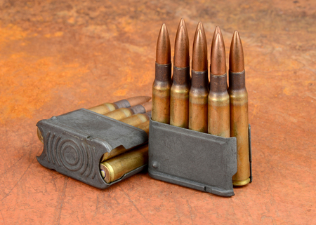 reloading: World War II  M1 Clips and 30-06 ammunition on rusty background.