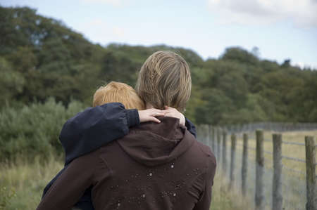 carying: mother carying her hugging son Stock Photo