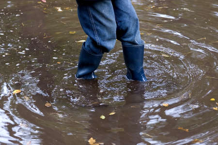 boy with rubber boots standing in the water photo