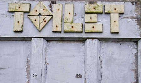 wooden letters spelling out toilet on old door Stock Photo - 695278