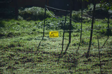 Yellow hazard warning sign on an electric fence hanging from a strand of wire in a rural environment with lush green vegetation