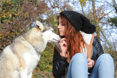 wolf couple: young woman with her dog in autumn