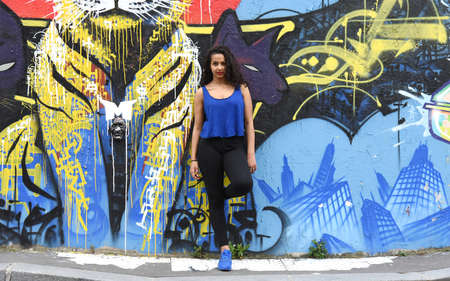 metis: young woman in front of a street art wall Stock Photo
