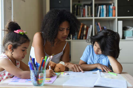 metis mother tutoring her children at home Stock Photo