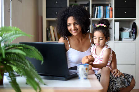 metis mother telecommuting at home with her daughter