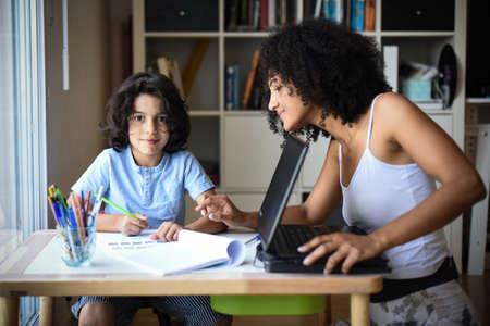 metis mother telecommuting at home while her son doing his homework