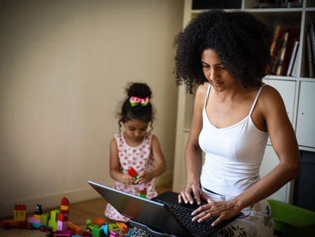 metis mother telecommuting at home while her daughter playing