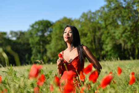 asian woman in poppy field Banque d'images