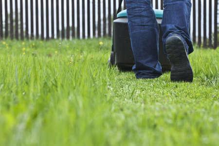 gras maaien: Man maaien gazon in zijn tuin in de zomer