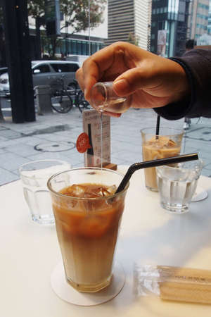 sweeten: Pouring syrup into ice coffee