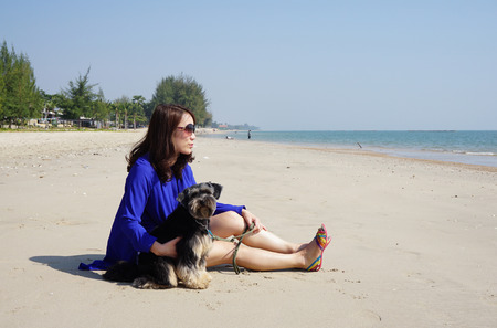seaboard: Woman with the little dog on the beach on the sunny day Stock Photo
