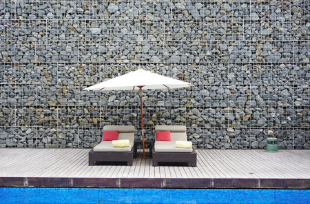 beach bed at the swimming pool with rock wall background photo