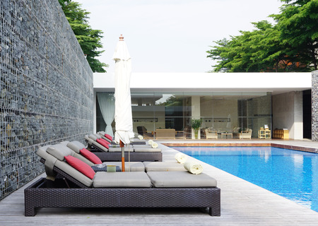 umbella: swimming pool with rock wall and beach chair