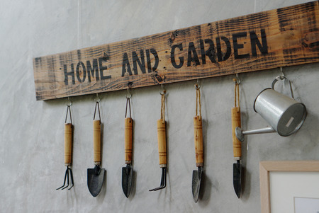 Small Garden Tools Hanging On The Concrete Wall With Home And Garden  Signage Stock Photo