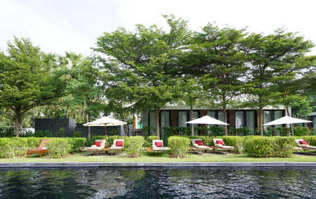 beach chair with parasol next to the pool with building and tree background 版權商用圖片